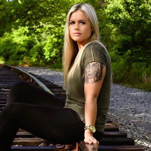 Blonde girl with green shirt sitting on train tracks